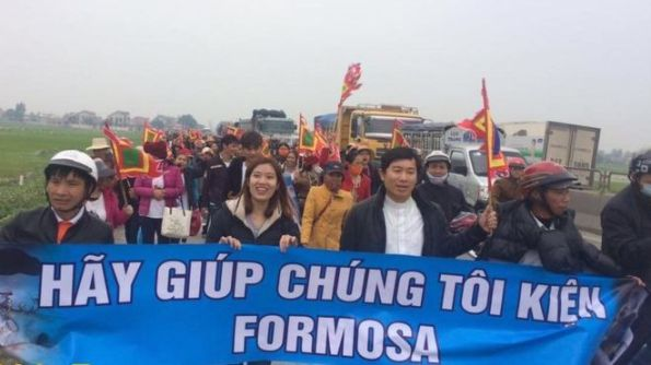 Linh mục Nguyễn Đình Thục (người cầm cờ ngũ sắc) dẫn đoàn tuần hành hôm 14/2/2017) - hình: GNsP